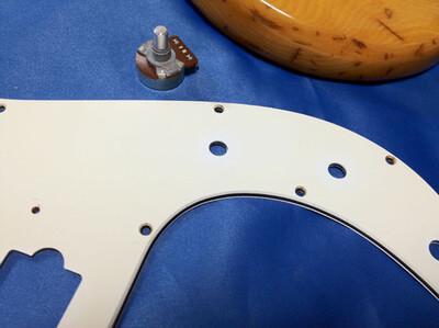 インチサイズのポットを付けるのでピックガードの穴を広げます